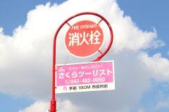 消火栓標識の広告看板「さくらツーリスト」